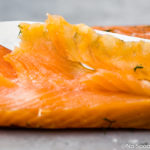 Straight on, landscape photo of a filet of salmon gravlax with a slicing knife and one single, thinly sliced piece of gravlax laying on top of the filet.