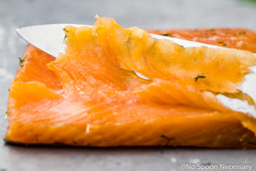 Straight on, landscape shot of a filet of gravlax, or cured salmon, with a slicing knife and one single, thinly sliced piece of gravlax laying on top of the filet.