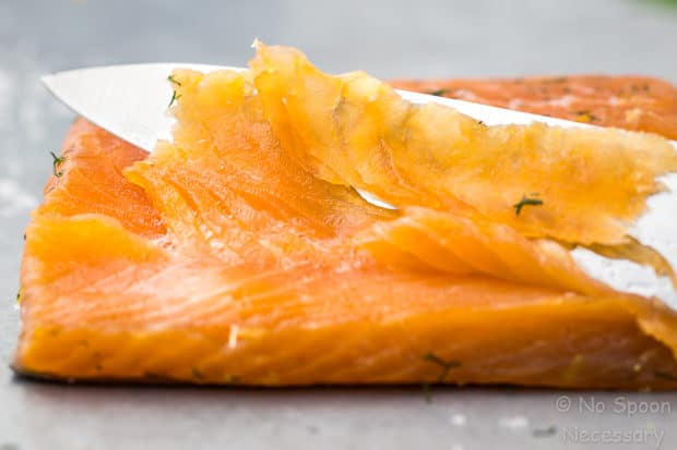Straight on shot of Gravlax with a knife slicing into the salmon - a main ingredient in Spring Salmon Pizza.