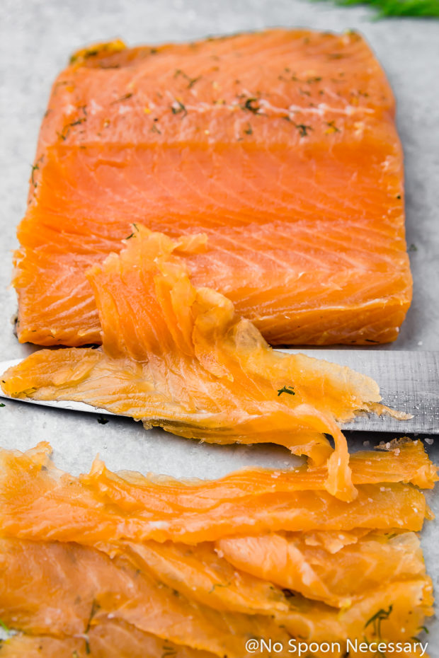45 degree angle shot of a filet of gravlax, or cured salmon, that has been partially carved and sliced on the bias, with the slicing knife laying in front of the salmon. (Showing how to slice gravlax or cured salmon at home)