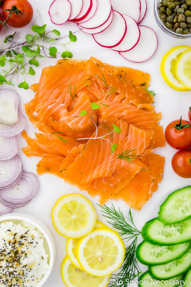 Overhead shot of a white surface neatly topped and organized with an array of cured salmon gravlax, sliced shallots, vine ripe tomatoes, sliced radishes, sliced lemons, sliced cucumbers, a small bowl of capers, fresh herbs and a bowl of everything spice cream cheese.