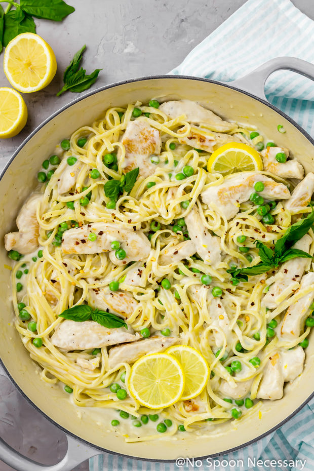 Overhead shot of a large gray skillet filled with One Pot Creamy Lemon Chicken Pasta with Basil & Peas with a pale teal stripped linen under the skillet and fresh basil leaves and lemon wedges in the upper corner of the shot.