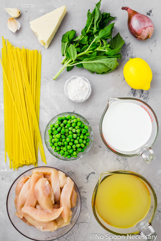 Overhead shot of all the ingredients needed to make One Pot Creamy Lemon Chicken Pasta with Basil & Peas neatly organized on a gray surface.