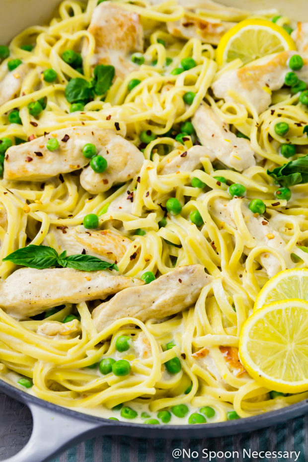Slightly angled, up close shot of One Pot Creamy Lemon Chicken Pasta with Basil & Peas in a large gray skillet.