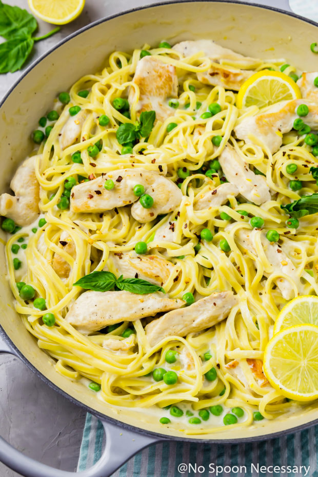 Overhead, slightly angled up close shot of a large gray skillet filled with One Pot Creamy Lemon Chicken Pasta with Basil & Peas with a pale teal stripped linen under the skillet.
