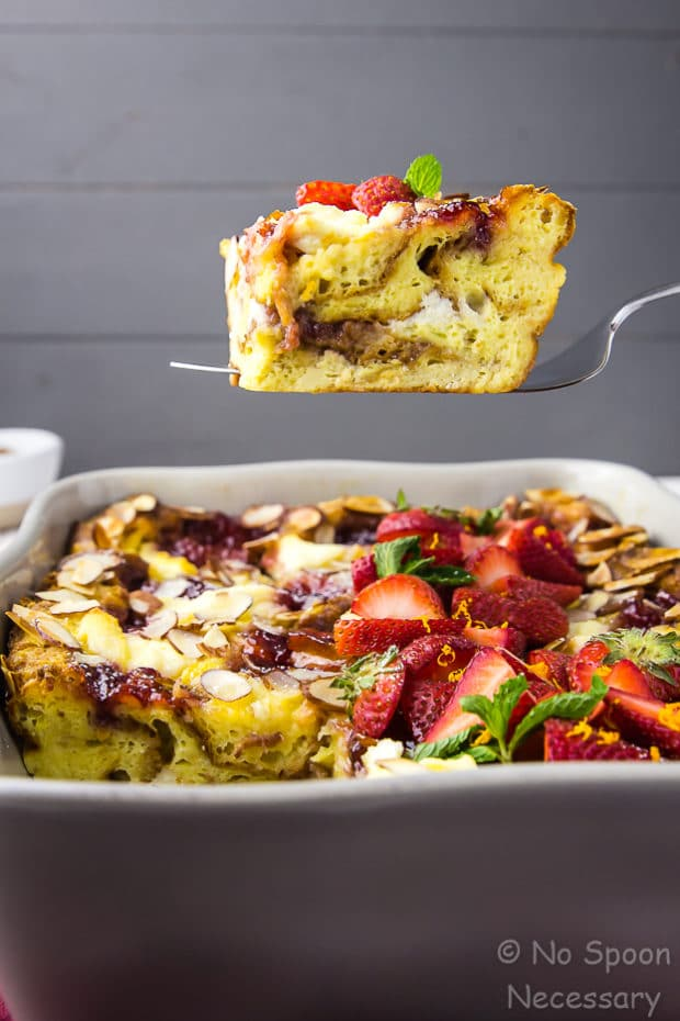 Straight on shot of a slice of Overnight Strawberry Ricotta Breakfast Strata being lifted with a spatula out of a gray baking dish.