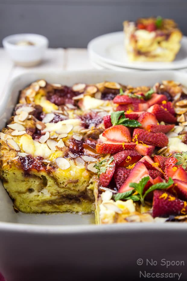 45 degree angle shot of a Overnight Strawberry Ricotta Breakfast Strata in a gray baking dish with a slice missing and placed on a plate blurred in the background.
