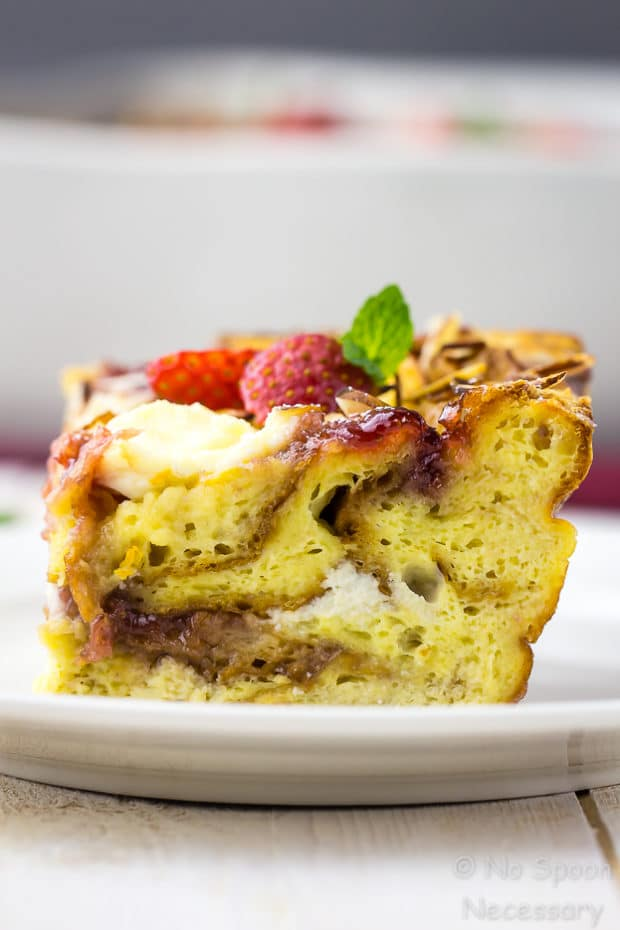 Straight on, up-close shot of a square slice of Overnight Strawberry & Ricotta Breakfast Strata on a white plate.