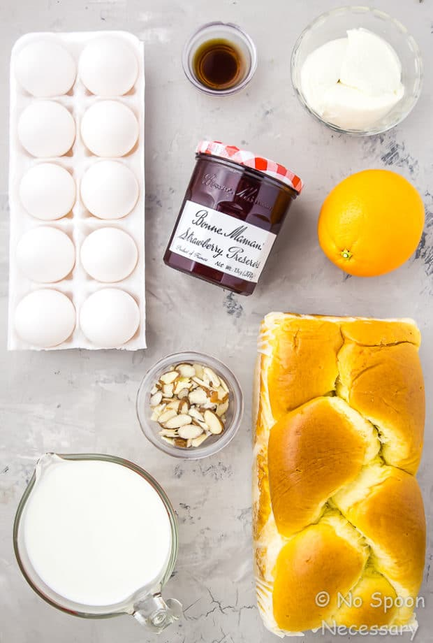 All the ingredients needed to make an Overnight Strawberry & Ricotta Breakfast Strata neatly organized on a gray surface.