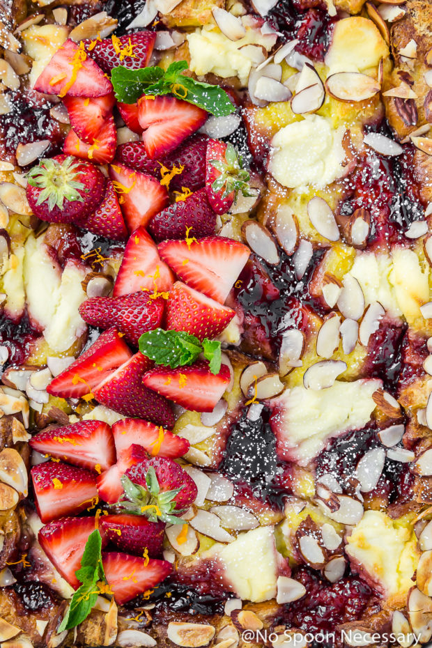 Overhead, upclose shot of the top of a Overnight Strawberry Ricotta Breakfast Strata garnished with fresh sliced strawberries and toasted sliced almonds.