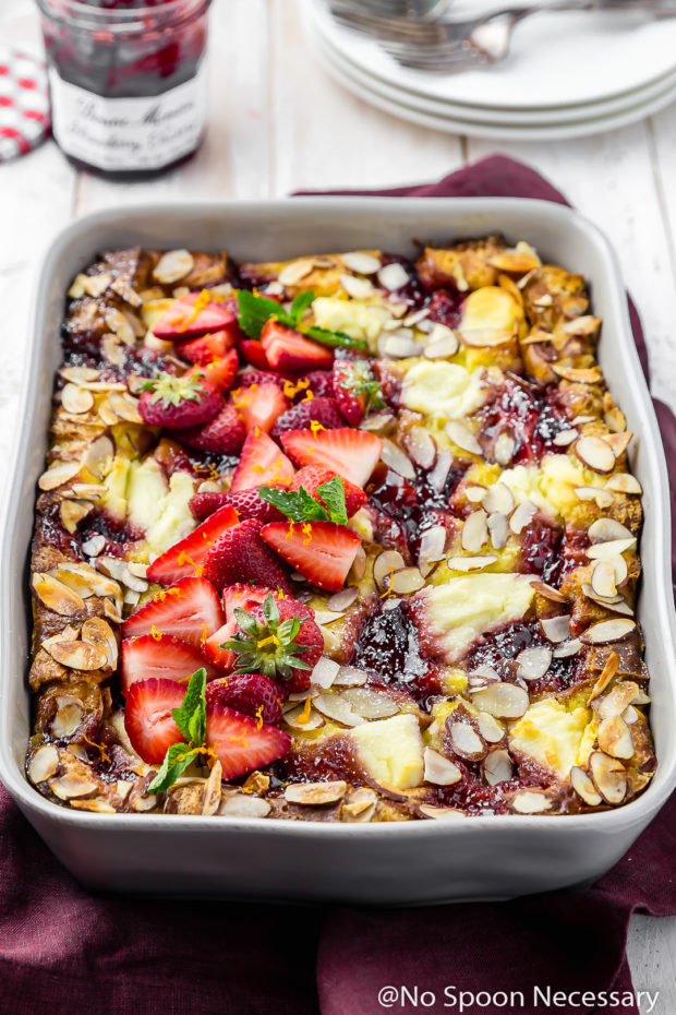 45 degree angle shot of Overnight Strawberry Ricotta Breakfast Strata in a gray baking dish on a red linen with a jar of strawberry preserves, stack of plates and forks blurred in the background.
