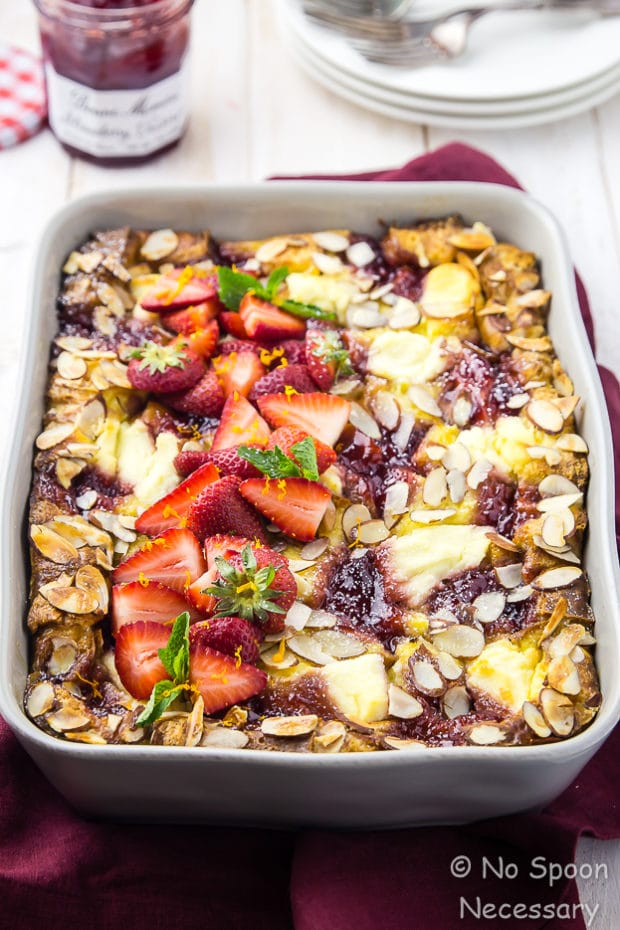 45 degree angle shot of Overnight Strawberry & Ricotta Breakfast Strata in a gray baking dish on a red linen with a jar of strawberry preserves, stack of plates and forks blurred in the background.