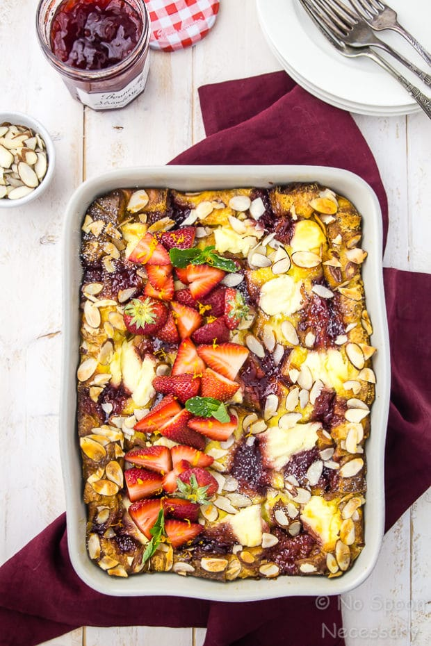 Overhead shot of Overnight Strawberry & Ricotta Breakfast Strata in a gray baking dish on a red linen with a small bowl of sliced almonds, a jar of strawberry preserves, plates and forks surrounding the baking dish.