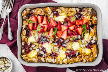 Overhead shot of Overnight Strawberry & Ricotta Breakfast Strata in a gray baking dish on a red linen with a small bowl of sliced almonds and forks surrounding the baking dish.