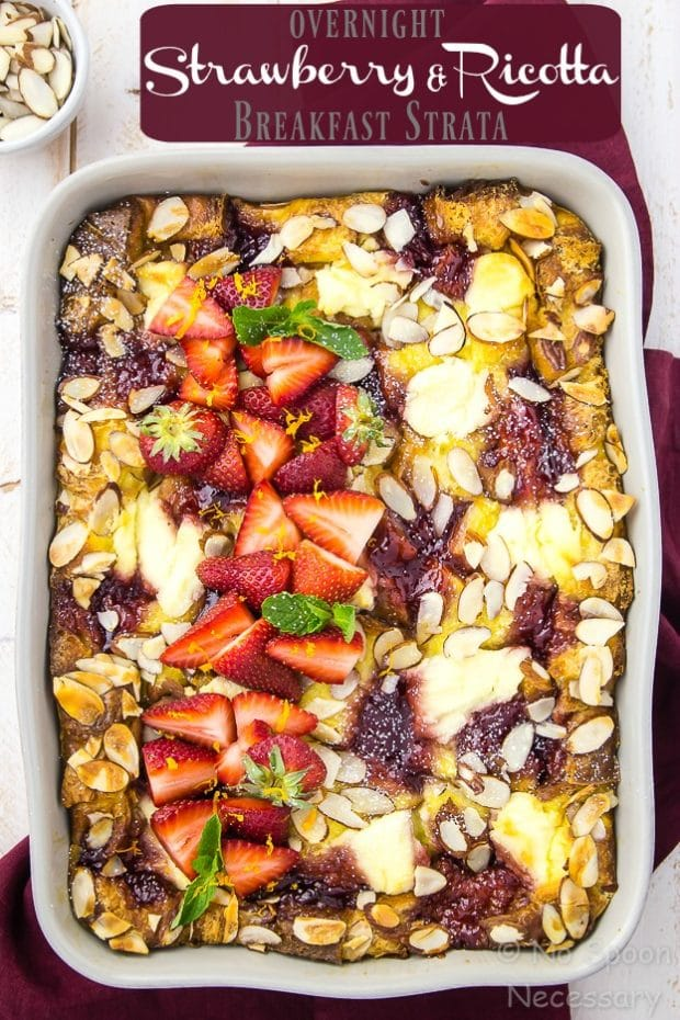 """Overhead shot of Overnight Strawberry & Ricotta Breakfast Strata in a light gray baking dish on a red linen with a ramekin of almonds tucked in the upper corner of the shot and the words """"Overnight Strawberry & Ricotta Breakfast Strata"""" written on the top of the shot."""