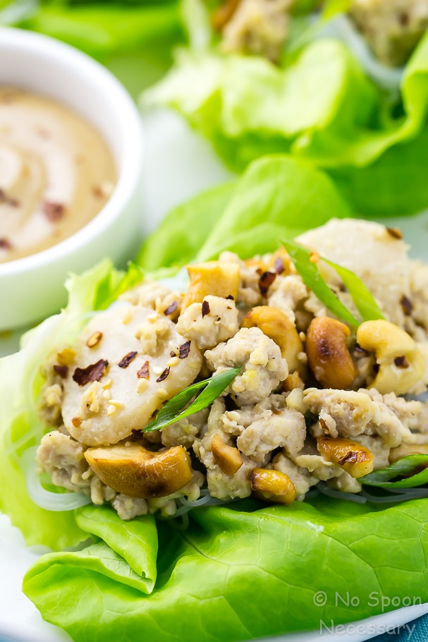 Angled close up shot of an easy cashew chicken lettuce wrap with tahini dipping sauce in the background