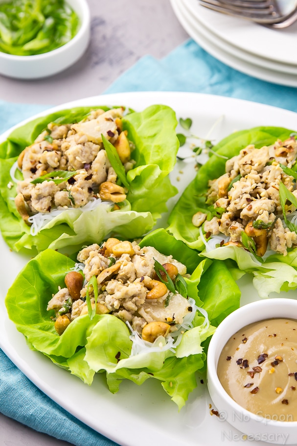 Angled shot of a platter of easy cashew chicken lettuce wraps with ramekins of tahini dipping sauce and scallions and plates with forks in the background