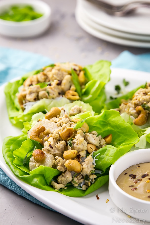 Straight on shot of a platter of easy cashew chicken lettuce wraps with plates, forks and a ramekin of scallions in the background