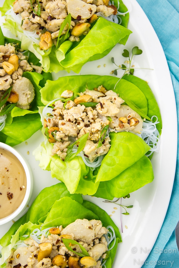 Overhead shot of one easy cashew chicken lettuce wrap and three partial lettuce wraps on the sides