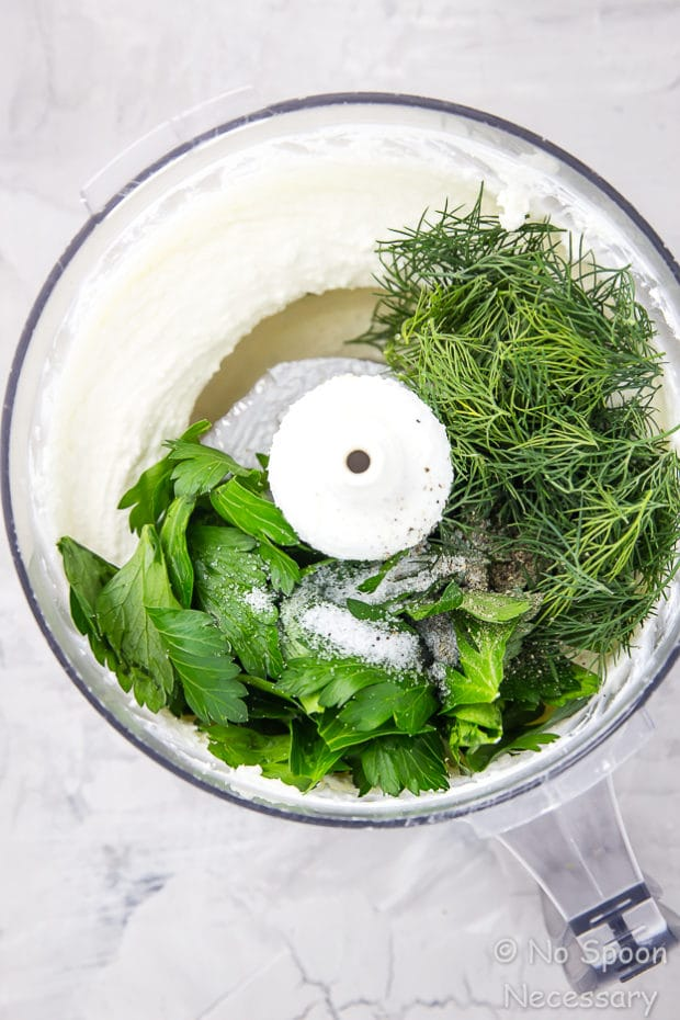 Overhead shot of a food processor bowl filled with the ingredients to make Whipped Herbed Feta dip.