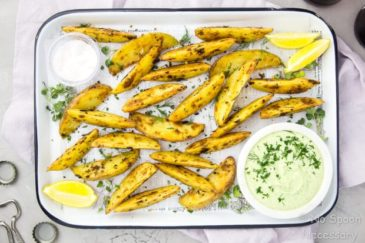 Overhead shot of a white tray of Crispy Baked Greek Potato Wedges with a bowl of Whipped Herbed Feta, ramekin of salt, lemon wedges and fresh herbs on a light purple linen; with beer bottles, caps and a bottle opener surrounding the tray.