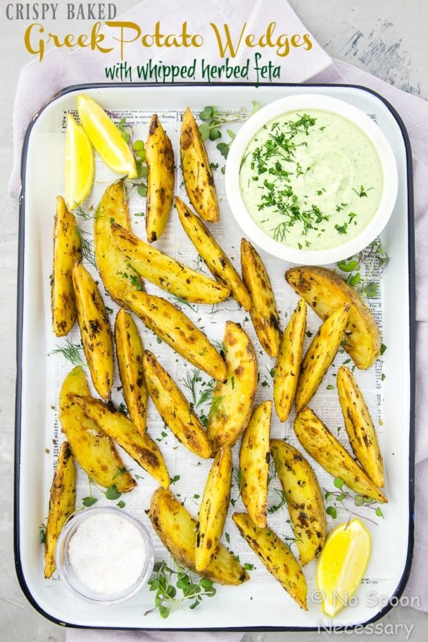Overhead shot of a white tray of Crispy Baked Greek Potato Wedges with a bowl of Whipped Herbed Feta, ramekin of salt, lemon wedges and fresh herbs on a light purple linen.