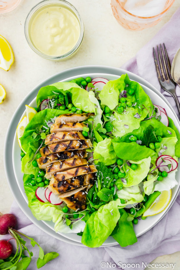 Overhead shot of a plate of Grilled Honey Chicken & Pea Salad with fresh radishes, a purple linen, lemon wedges, water glasses and a jar of creamy mustard vinaigrette surrounding the plate.