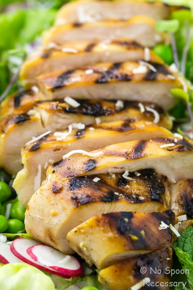 Angled, up close shot of sliced Grilled Honey Chicken on a Pea Salad.