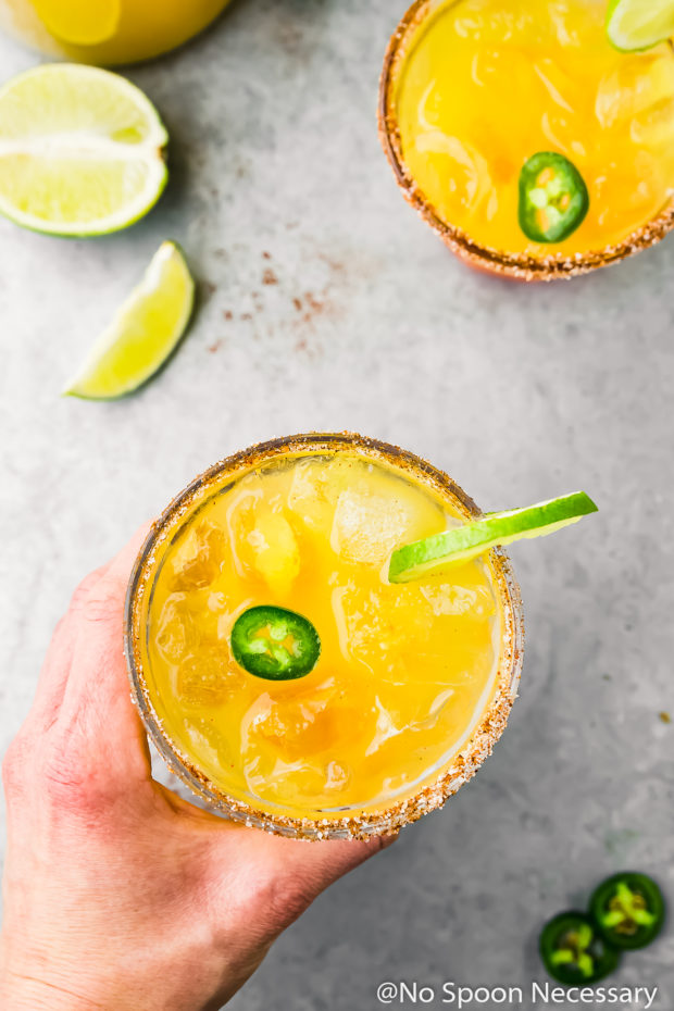 Overhead shot of two rocks glasses filled with Spicy Mango Margarita garnished with sliced jalapeno and slices of lime with a hand holding one of the margaritas and lime wedges tucked in the upper left hand corner of the shot.