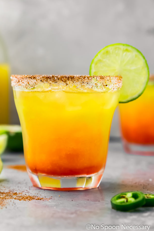 Straight on shot of a rocks glass filled with a Spicy Mango Margarita garnished with a slice of lime with slices of jalapenos, lime wedges and another margarita blurred in the background.
