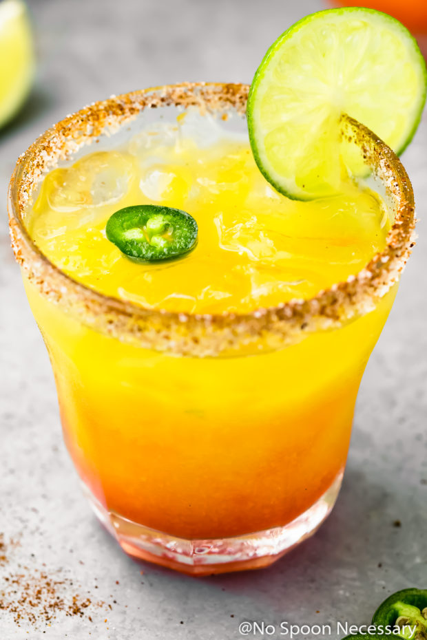 45 degree angle shot of a rocks glass filled with a Spicy Mango Margarita garnished with a slice of lime and slice of jalapeno; with a lime wedge blurred in the background.