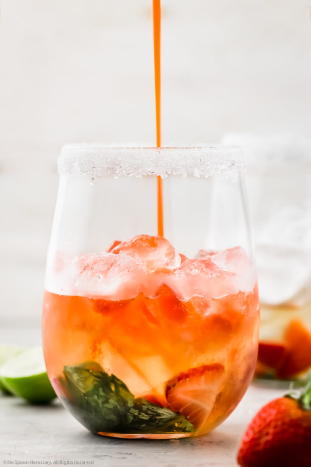Straight on photo of a Strawberry Basil Vodka Cocktail being poured into a cocktail glass filled with ice, fresh basil and fresh strawberries.