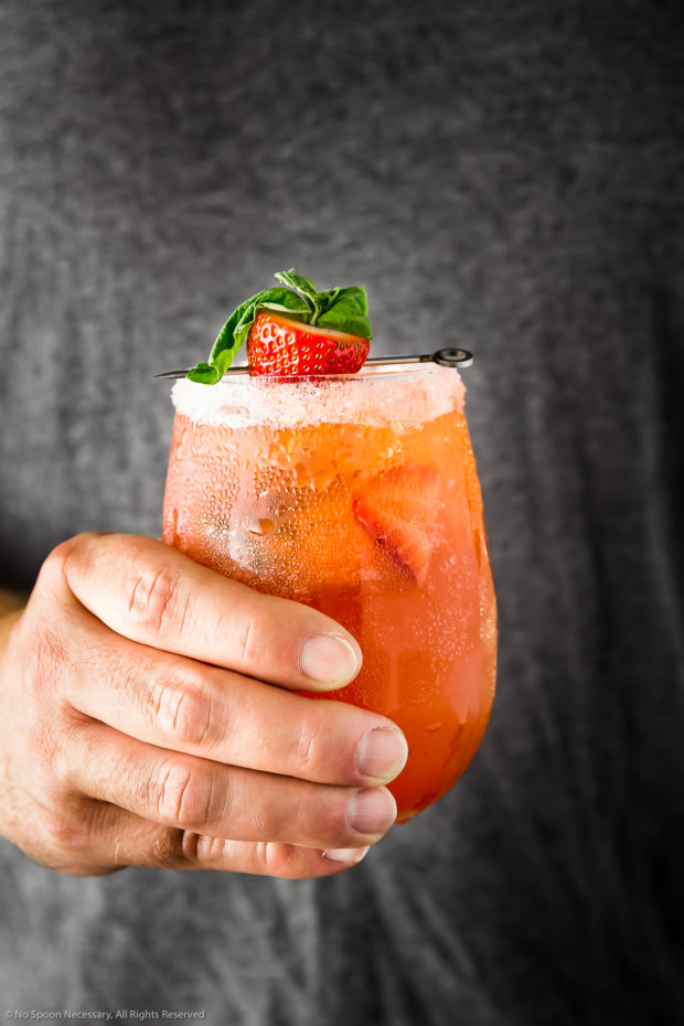 Straight on photo of a hand holding a fresh berry cocktail.