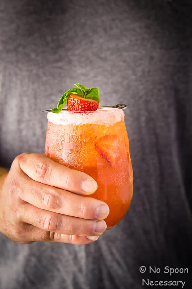 Straight on shot of a hand holding a Strawberry Basil Vodka Cocktail.