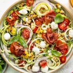 Overhead photo of Zucchini Salad topped with corn, tomatoes, mozzarella pearls and crispy prosciutto in a large white serving bowl with a jar of homemade Italian dressing and ramekin of fresh basil next to the bowl.