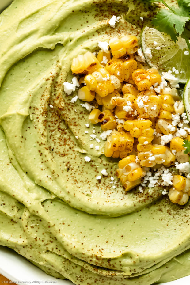 Overhead up close photo of creamy avocado hummus topped with spicy seasoning, charred corn and crumbled cheese.