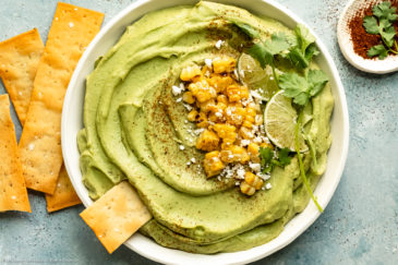 Overhead landscape photo of Spicy Avocado Hummus topped with charred corn, crumbled cheese, lime wedges and fresh cilantro in a large white serving bowl with pita strips and a ramekin of sriracha powder next to the bowl.