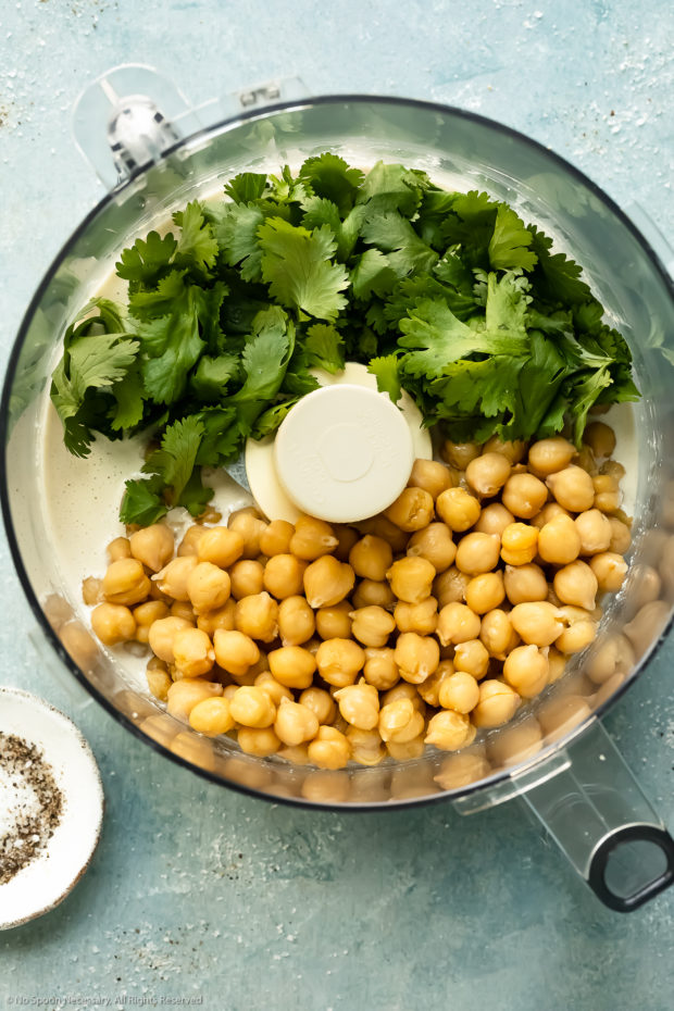 Overhead photo of a food processor bowl filled with whipped tahini and topped with cooked chickpeas and fresh cilantro - photo of step 4 of the recipe