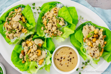 Overhead, landscape shot of Cashew Chicken Lettuce Wraps on a white platter with a small ramekin of tahini sauce on a light blue linen with a small ramekin of sliced scallions next to the platter.