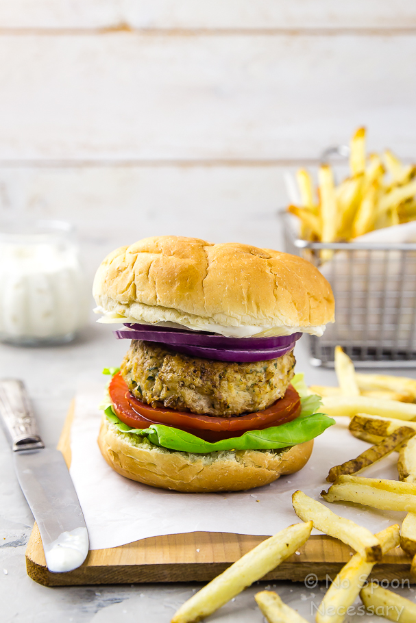 Straight on shot of a Chicken Caesar Burger next to a knife and fries with a jar of Parmesan Peppercorn Sauce and a basket of french fries in the background