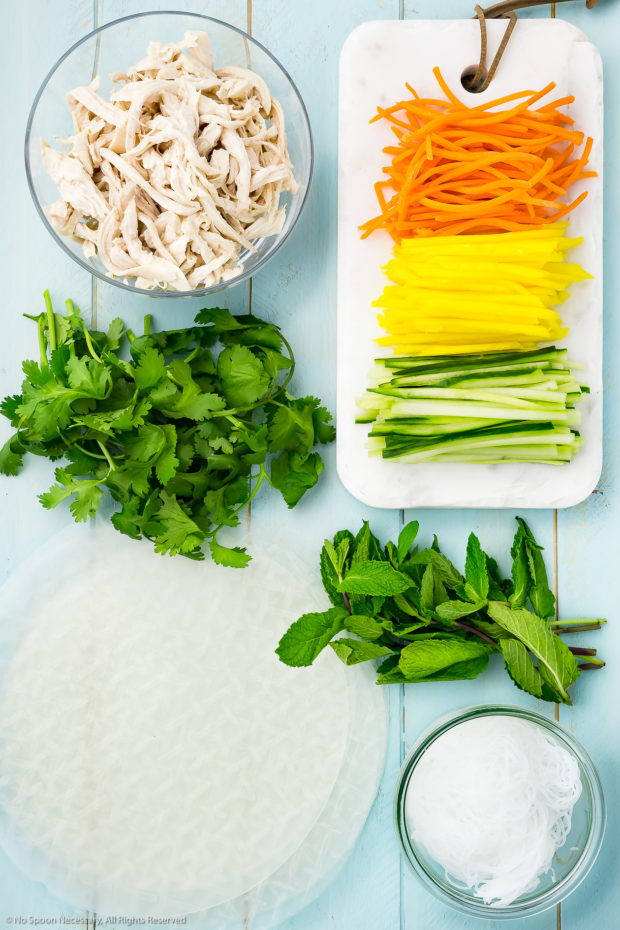 Overhead photo of all the ingredients needed to make chicken fresh spring rolls recipe neatly organized by individual ingredient on a pale blue wood surface.