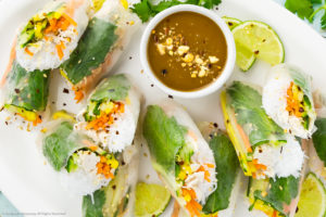 Overhead photo of Chicken Rice Paper Rolls with slices of lime and a small ramekin of peanut sauce on a large white serving platter.