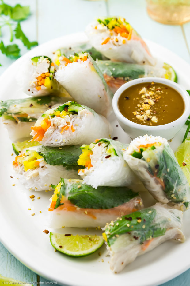 Angled photo of Chicken Rice Paper Rolls with slices of lime and a small ramekin of peanut sauce on a large white serving platter.