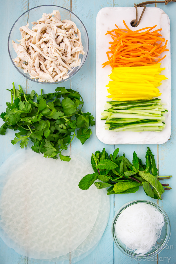Overhead shot of the ingredients to make Coconut Chicken and Mango Summer rolls. Coconut poached chicken in a glass bowl, slices of carrot, mango and cucumber on a small white tray; rice paper wrappers, a bowl of rice noodles and a bundle of cilantro and mint