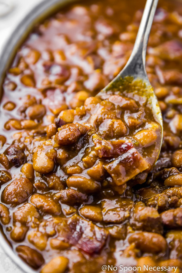 Close-up angled shot of Homemade Bacon Bourbon & Brown Sugar Baked Beans in a galvanized bucket being scooped and served with a spoon.