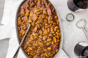 Overhead, landscape shot of Homemade Bacon Bourbon & Brown Sugar Baked Beans in a galvanized bucket with a serving spoon. White linen, beer bottles, caps and beer opener in background.