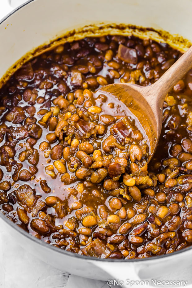 Angled shot of Homemade Bacon Bourbon & Brown Sugar Baked Beans in a large pot being stirred with a wooden spoon.