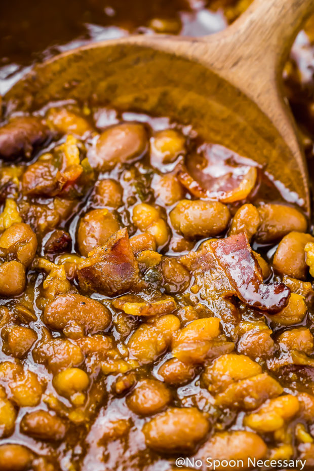 Extreme close-up shot of Homemade Bacon Bourbon & Brown Sugar Baked Beans being stirred with a wooden spoon.