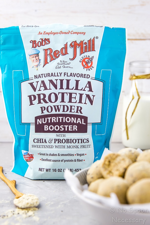 Straight on shot of a bag on Bob's Red Mill Vanilla Protein Powder with a bowl of energy protein bites and a wooden spoon of protein powder in the forefront