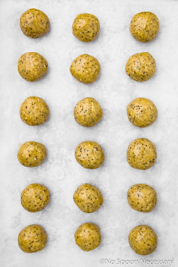 Overhead photo of No Bake Honey Nut Vanilla Protein Energy Bites on a parchment paper lined sheet pan before freezing - photo of step 5 of the recipe.